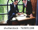 Small photo of Two businessman working together about documents, partner discuss plan or idea and opinion meeting, Asian bussiness are discussing their working on wood table beside window at coffee shop
