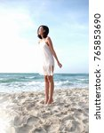 Small photo of Asian lady standing tiptoe on the beach
