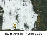 Small photo of Woman adventurer happy raised hands enjoying big waterfall landscape outdoor Travel Lifestyle success concept adventure scandinavian vacations wild nature