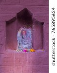 Small photo of Vertical photo of hindu deity Ganesh stone statue in pink niche with offerings of flowers and red powder in Bandipur, Nepal
