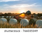 at sunset  a tractor loads... | Shutterstock . vector #766035349