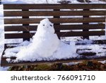 Snowman On Wooden Bench.