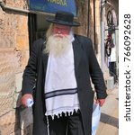Small photo of JERUSALEM, ISRAEL - Mar.24, 2010: An elderly Orthodox Jew, dressed in black garb and a tallit (prayer shawl) walks along a street in downtown Jerusalem.