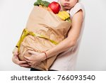 Small photo of Close up of a woman holding heavy bag with groceries wrapped with a measuring tape isolated over white background