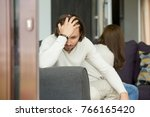 Small photo of Upset man thinking of unresolved problems fed up with misunderstandings in bad relationships sitting his back to frustrated woman on sofa at home holding head in hand, unhappy couple after quarrel