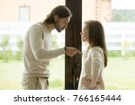 Small photo of Unhappy young couple arguing standing at house door, angry husband pointing at wife blaming her of problems, conflicts in marriage, bad relationships, man and woman having quarrel or disagreement