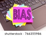 Small photo of Writing Bias text made in the office close-up on laptop computer keyboard. Business concept for Prejudice Biased Unfair Treatment Workshop on the black background with space