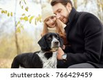 couple walking with dog in the... | Shutterstock . vector #766429459