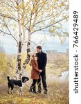 couple walking with dog in the... | Shutterstock . vector #766429489