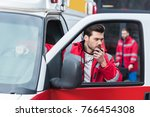 Small photo of handsome male paramedic talking by portable radio and standing close to ambulance