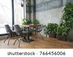 Stock photo interior shot of cafeteria with modern design and furniture decorated with plenty of green plants 766456006