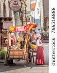 Small photo of Tallinn, Estonia; 24th July 2016; Two Young Women in Traditional Dress Selling Food From Wooden Cart