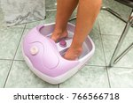 female feet in a vibrating foot ... | Shutterstock . vector #766566718