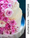white wedding cake with flowers  | Shutterstock . vector #766629166