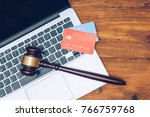 Small photo of Handcuffs, judge gavel and credit cards on laptop keyboard. Concept of internet crime, hacking, cyber crimes and virtual payments