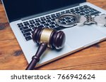 Small photo of Handcuffs and judge gavel on computer. Concept of internet crime, hacking and cyber crimes
