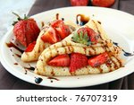 sweet thin french style crepes, served with strawberries,chocolate sauce - stock photo