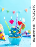 Small photo of Colorful decorated cupcake with candles alight. Birthday card mockup.
