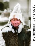 Small photo of BOROVETS, BULGARIA - CIRCA DECEMBER 2011: A male mountaineer dressed in a national dress made of natural pelage with a fur hat smiles