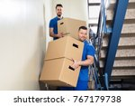 two young male movers in blue... | Shutterstock . vector #767179738