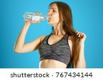 sporty girl drinking water from ... | Shutterstock . vector #767434144