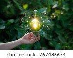 Hand Holding Light Bulb Agains...