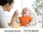 mother feeding her baby son... | Shutterstock . vector #767518603