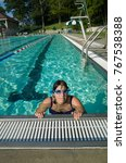 Small photo of Woman in a swimming pool lap lane