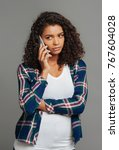 Small photo of Waiting for news. Waist up of a cheerless young woman having a serious talk on smartphone