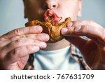 man eats burger close up | Shutterstock . vector #767631709