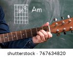 Small photo of Man in a blue denim shirt playing guitar chords displayed on a blackboard, Chord Am