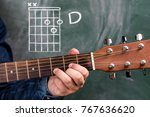 Small photo of Man in a blue denim shirt playing guitar chords displayed on a blackboard, Chord G