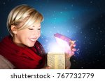attractive woman opening a gift | Shutterstock . vector #767732779