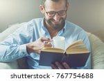 smiling man reading interesting ... | Shutterstock . vector #767754688
