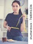 young woman measuring waist at...   Shutterstock . vector #768041236