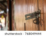 Small photo of Old hasp on the wooden accordion door of one waterfront house at Amphawa, Thailand.