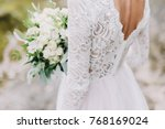 bride holds a wedding bouquet ... | Shutterstock . vector #768169024