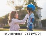 asian mother helping her son... | Shutterstock . vector #768194704