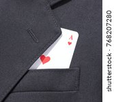 Small photo of Ace of hearts playing card in business man black suit pocket