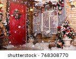 Small photo of Christmas decor on a patio. Doors are decorated by a festive chaplet and toys. Fir-tree at a window, snow
