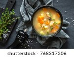 Fresh fish soup in bowl on black background, top view