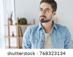 Small photo of Fashionable young male worker or manager wears spectacles, stylish denim shirt, has thoughtful expression, looks with clever look aside, stands over home or office interior. Facial expressions concept