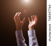 Small photo of Male arms and hands raised and outstretched in the air to divine light. Man praying, begging, pleading imploring or supplicating. Black background. Businessman with Christian Catholic religious faith