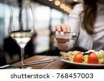woman adding salt to food in... | Shutterstock . vector #768457003