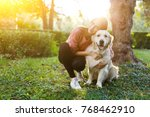 Stock photo image of woman hugging dog on lawn 768462910