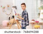 little boy painting ship at home | Shutterstock . vector #768694288