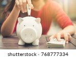 woman hand putting money bank... | Shutterstock . vector #768777334