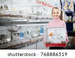 Stock photo smiling girl customer happy about buying cage with canary bird in pet shop 768886519
