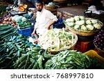 Small photo of MYSORE, INDIA - March, 2014: Mysore market, Indian man selling vegetables and greenery at Devaraja market, Mysore, India