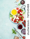 Small photo of Italian antipasti snack for wine. Mozzarella cheese, fresh basil leaves, tomatoes, olive oil and glasses of red wine on concrete background, top view. Caprese salat